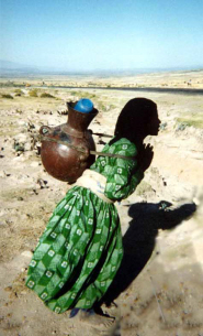 An Ethiopian woman carries water home from the village tap  Image by Dr Mhairi Gibson
