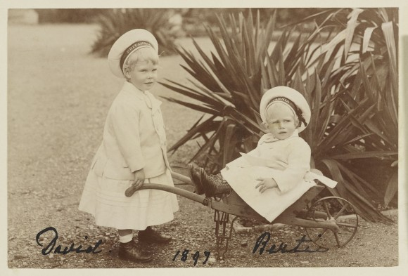 Photograph of Prince Edward of York (1894-1972), later the Duke of Windsor, standing in three-quarters right whilst holding the arms of a wheelbarrow in which Prince Albert of York (1895-1952), later King George VI, is sitting. Both children wear sailors hats with a band around the rim that bears the name 'Britannia', the Royal Cutter built in ... Royal Collection Trust/© Her Majesty Queen Elizabeth II 2014