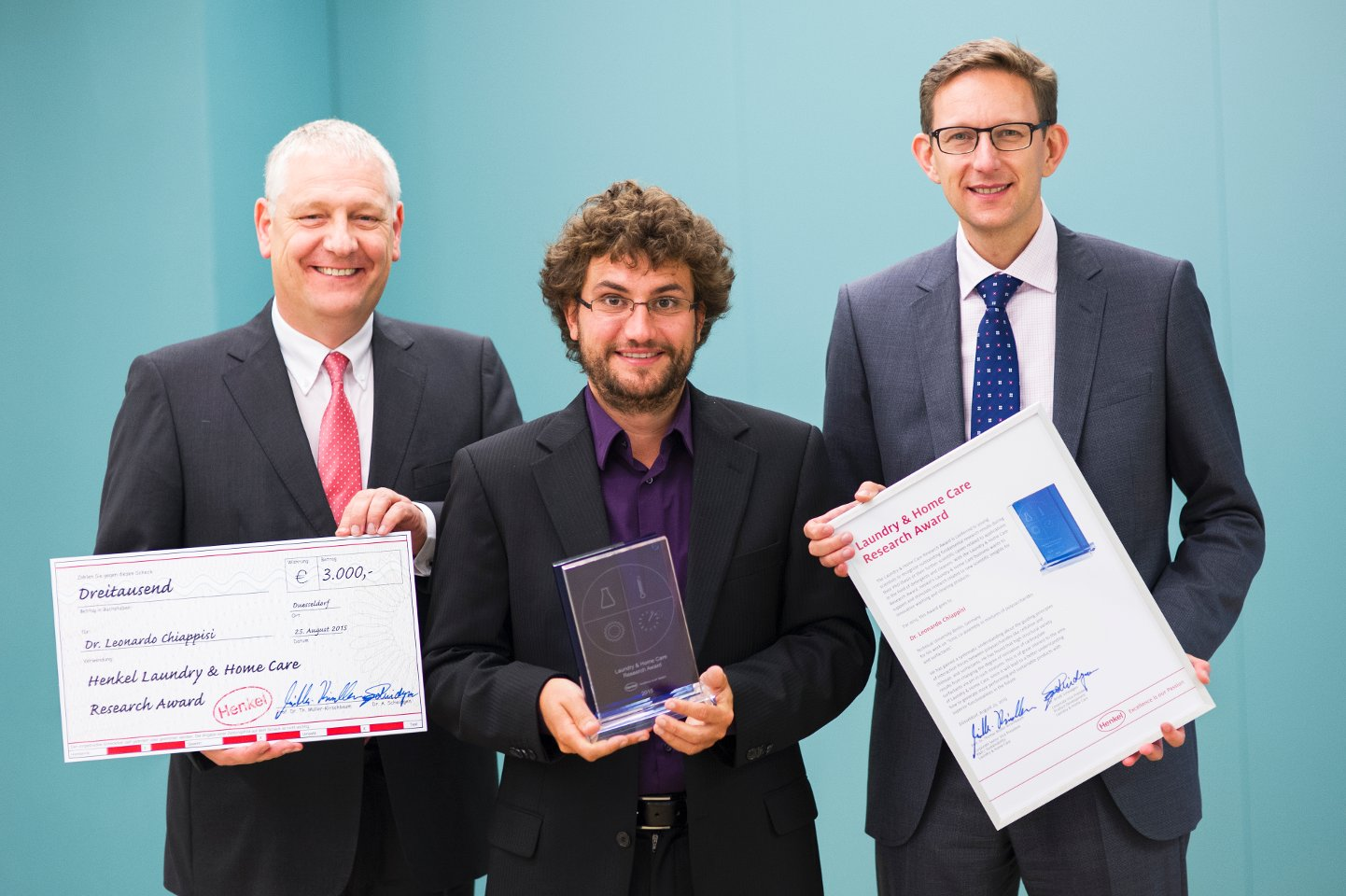 "Prof. Dr. Thomas Müller-Kirschbaum (left), Head of Global Research and Development at the Laundry & Home Care business unit, and Dr. Michael Dreja, Head of Global Research at Laundry & Home Care, present the ""Laundry & Home Care Research Award 2015"" to Dr. Leonardo Chiappisi (center)."