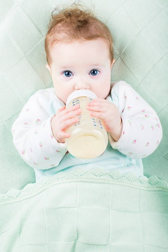 Beautiful little baby with a milk bottle under a warm knitted blanket