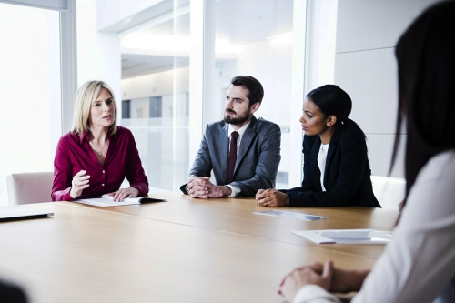 Mature female business professional talking to colleagues in boardroom. Businesswoman speaking to executives in company meeting. Group of modern business people