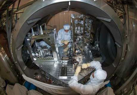 Researchers installing some of the small suspended LIGO mirrors in the vacuum system (Credit: Courtesy of LIGO Laboratory)